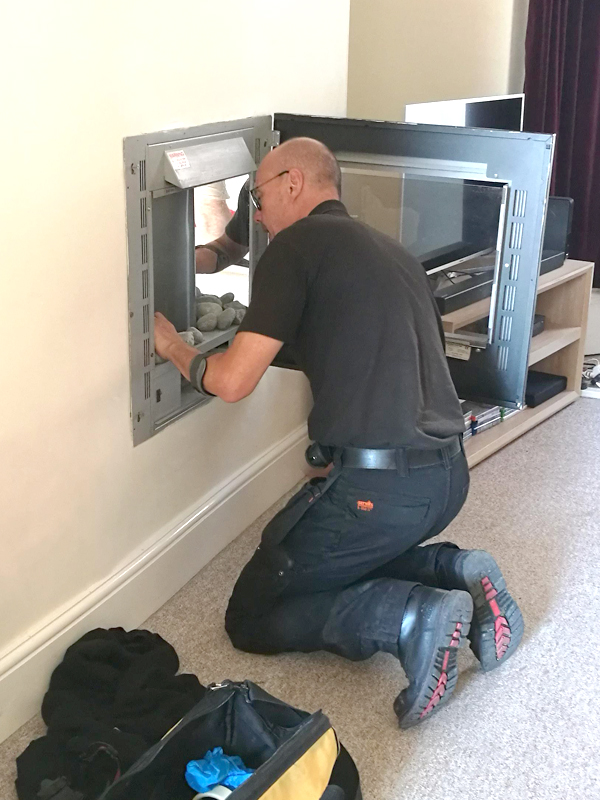 Isca Pest Control's Darren accessing behind the fireplace to rescue the chick